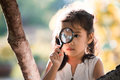 Asian little child girl looking through a magnifying glass Royalty Free Stock Photo