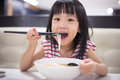 Asian little Chinese girl eating noodles soup Royalty Free Stock Photo