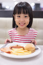 Asian Little Chinese Girl Eating Western Food Royalty Free Stock Photo