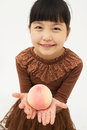 Asian little girl with peach isolated on white background Stock Photos