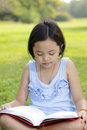 Asian little girl reading book park Stock Images