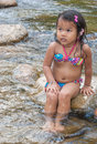 Asian little girl sitting near the waterfall Royalty Free Stock Images