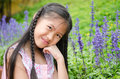 Asian little girl squat in flowers the park Royalty Free Stock Photos