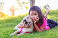 Asian Little girl with a yellow labrador puppy in a park, outdoo Royalty Free Stock Photo