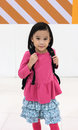 Asian little kid girl on pink t-shirt and blue skirt with backpa Royalty Free Stock Photo