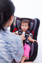 Asian lovely girl at car seat and fasten seat belt image of mother with security to her little thai in safety on white background Royalty Free Stock Images