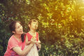Asian lovely girl and her mother blowing soap bubbles. Family at Royalty Free Stock Photo