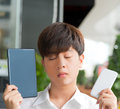 Asian male decide and hesitate to use smart device tablet or smartphone close his eyes Stock Photo