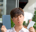 Asian male decide and hesitate to use smart device tablet or smartphone see above Royalty Free Stock Image