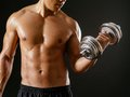 Asian male doing bicep curls photo of an exercising with dumbbells and over dark background Stock Photo