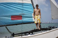 Asian male retiree standing proudly on his sail boat in sailing sports Stock Images