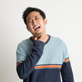 Asian male sore throat with painful face expression on plain background Stock Photography