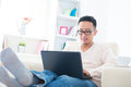 Asian male using internet at home Royalty Free Stock Images