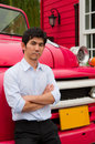An asian man cross his arm and lean against truck pink Stock Images