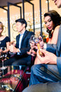 Asian man cutting cigar in restaurant sitting with friends and Royalty Free Stock Photography