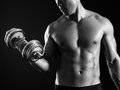 Asian man doing a bicep curl photo of an male exercising with dumbbell and curls over dark background Royalty Free Stock Image