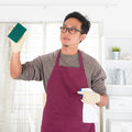 Asian man doing house chores guy housekeeping husband with home interiors male model Royalty Free Stock Images