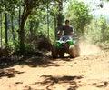Asian Man Driving All-Terrain Vehicle on Jungle Stock Photo