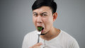 An Asian man eats broccoli. Royalty Free Stock Photo