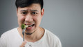 An Asian man eats broccoli. Royalty Free Stock Photo