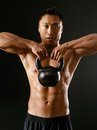 Asian man exercising with kettlebell photo of an male a kettle bell over dark background Royalty Free Stock Photo