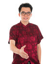 Asian man gives a handshake in traditional chinese cheongsam or tang suit extending hand to give standing isolated on white Royalty Free Stock Photo