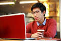 Asian man in glasses working on laptop young and holding cup of coffee Stock Image