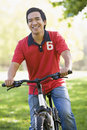 Asian man riding bike in park Stock Photos