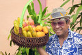 Asian man selling fruit from a basket portrait of smiling filipino wearing fedora hat tinted sunglasses and flower shirt holding Stock Images