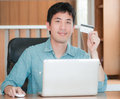 Asian man shopping online holding credit card and using laptop concept Stock Images
