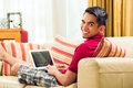Asian man sitting on couch surfing the internet Royalty Free Stock Photo