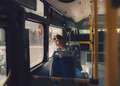 Asian man sitting dreaming on bus looking through window. Royalty Free Stock Photo