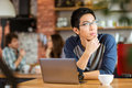 Asian man sitting with laptop in cafe and looking away thoughtful handsome young men glasses Stock Image