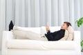 Asian man using handphone lying on sofa and Stock Photos