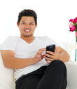 Asian man using handphone sitting on sofa and Royalty Free Stock Images