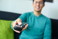 Asian man watching tv changes channel with remote young adult and changing control narrow focus on buttons and hand in foreground Stock Photos
