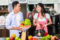 Asian man and woman cooking together Royalty Free Stock Photo