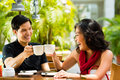Asian man and woman in restaurant or cafe men women having fun drinking hot beverage Stock Images