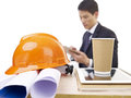 Asian manager young executive working in office with blueprints and safety hat focus on hat Stock Photo