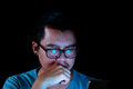 Asian men are using the phone or tablet with a blue light in the darkness Royalty Free Stock Photo