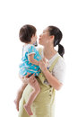 Asian mother carrying and soothe her daughter on white backgroun child holding electronic gadget isolated background Royalty Free Stock Images