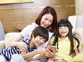 Asian mother and children using mobile phone together Royalty Free Stock Photo