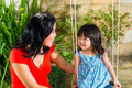 Asian mother and daughter at home in garden indonesian little girl her the playing on a swing Royalty Free Stock Photos