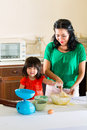 Asian mother and daughter at home in kitchen indonesian little girl her the bake a cake together Royalty Free Stock Photo