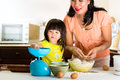 Asian mother and daughter at home in kitchen indonesian little girl her the bake a cake together Royalty Free Stock Images