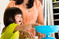 Asian mother and daughter at home in kitchen indonesian little girl her the bake a cake together Stock Image