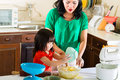 Asian mother and daughter at home in kitchen indonesian little girl her the bake a cake together Royalty Free Stock Image