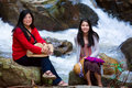 Asian mother and daughter sitting by river on boulder riverside Stock Photo