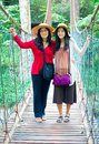 Asian mother and daughter standing on wooden hanging bridge in f together forest Stock Photography