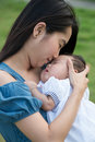 Asian mother kissing the cute baby in playground Stock Photography